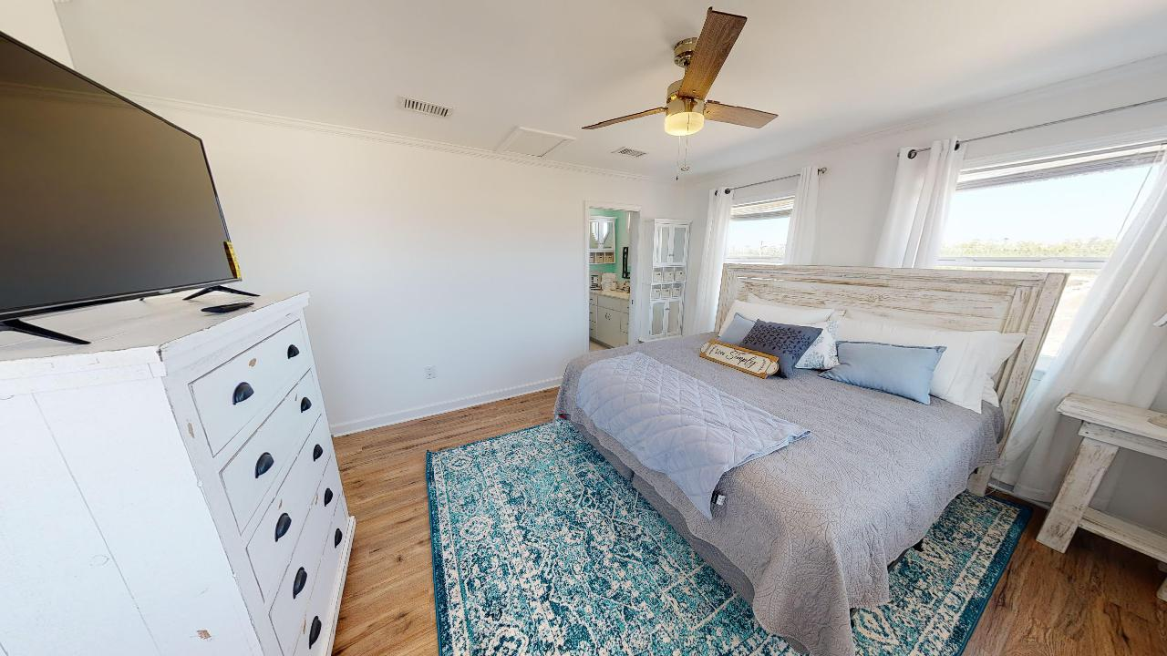 Spacious master suite with single bed and dresser top TV