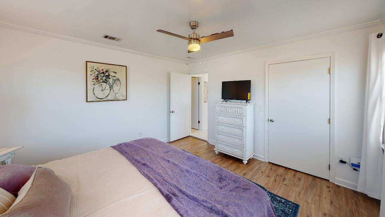King sized bed in bedroom 2 with ceiling fan and nearby tv