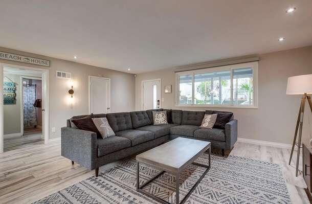 Sectional Sofa, TV, Coffee Table, Floor Lamp, Windows, and Door.