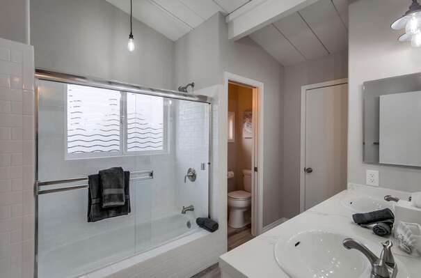 Shower-Tub Combo, Toilet, Mirror, and Double Sink Vanity.