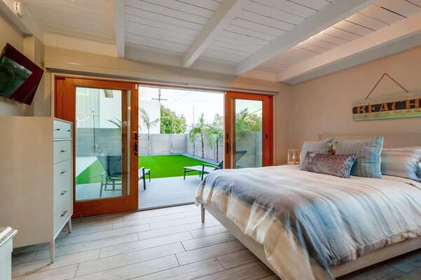 Bedroom with Large Bed, TV, Dresser, and Sliding Doors to the Backyard.