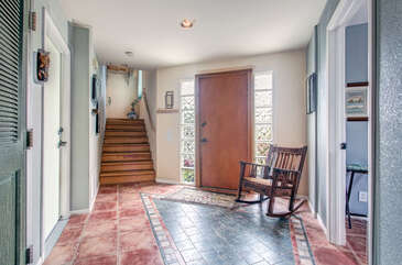 Enter the home into this large open entry with a rocking chair.