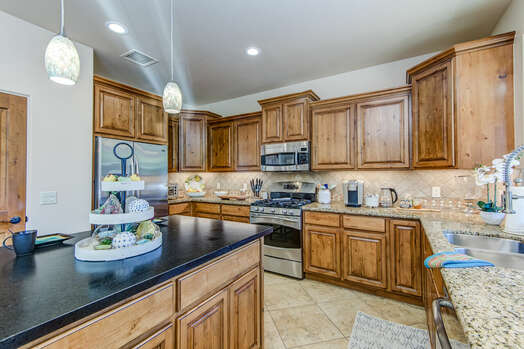 Spacious and Fully Equipped Kitchen Featuring Alder Wood Cabinets and Granite Counters