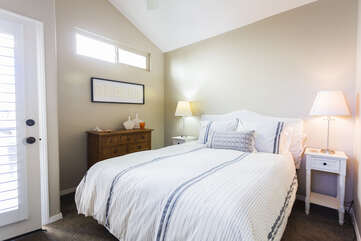 Guest bedroom with a queen bed that offers a balcony