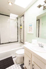Bathroom in hallway with shower-tub combo and a skylight over the sink area.