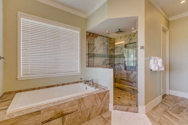 The ensuite bathroom has a garden tub and a walk-in shower