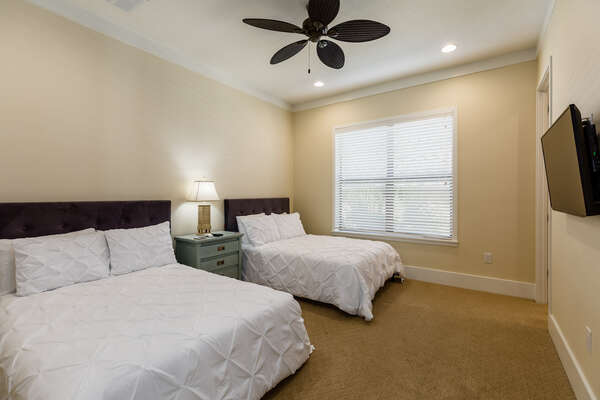 This bedroom has 2 full beds and a TV