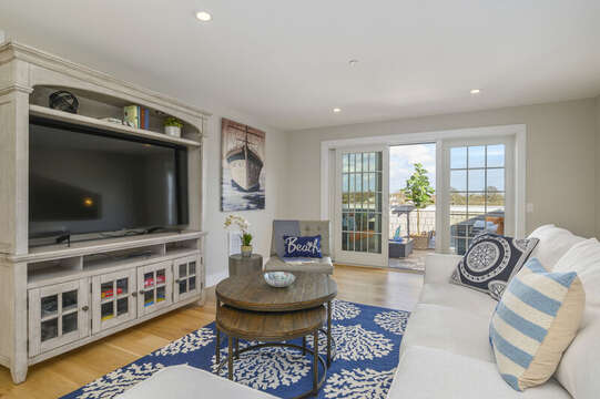 Large Flat Screen TV with comfy seating with entrance to the roof top terrace. Unit 201, 557 Route 28 Harwich Port, Cape Cod, New England Vacation Rentals