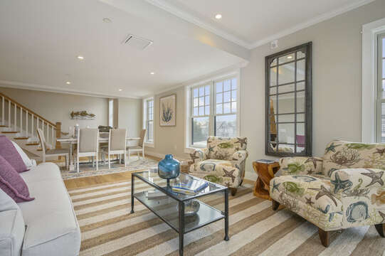 Living room with ample comfortable seating, opens to dining room. Unit 202, 557 Route 28, Harwich Port Cape Cod, New England Vacation Rentals.
