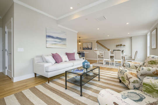 Open concept living and dining room with stairs to the second floor bonus room and roof top  deck. Unit 202, 557 Route 28, Harwich Port, Cape Cod New England Vacation Rentals