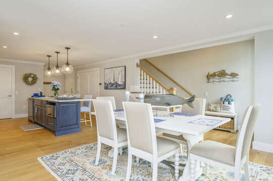 Open concept Dining room and kitchen with stairs to upper level. Unit 202, 557 Route 28, Harwich Port, Cape Cod, New England Vacation Rentals.