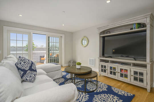 Second floor bonus room with large sectional and flat screen tv and entrance to roof top terrace with ample seating and views of Harwich Port.Unit 202, 557 Route 28, Harwich Port, Cape Cod, New England Vacation Rentals