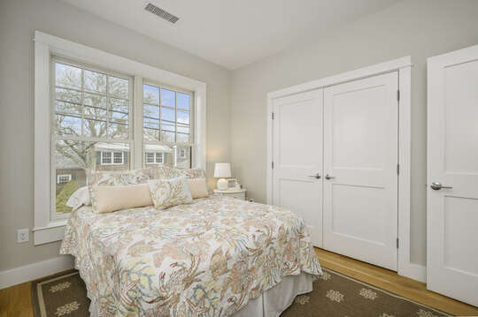 Queen bed with large closet and nightstand with views of Main St. Unit 202, 557 Route 28, Harwich Port,Cape Cod, New England Vacation Rentals