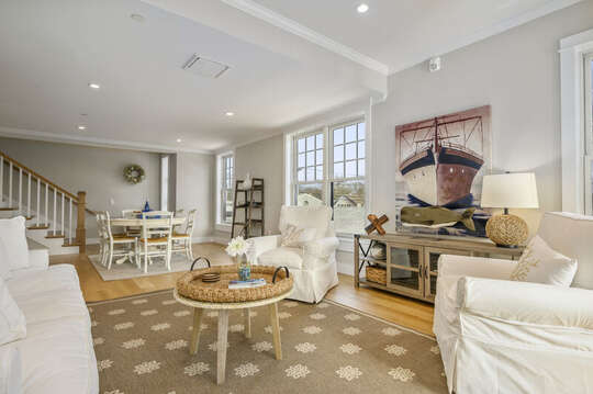 Living room with comfy seating on either the occasional chairs or couch opens to the dining area. Unit 203, 557 Route 28, Harwich Port, Cape Cod, New England Vacation Rentals