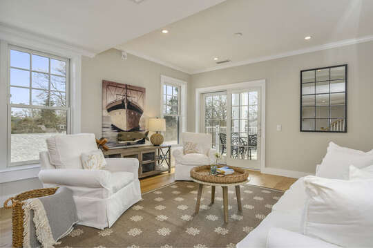 Living room with plenty of comfy seating and entrance to private balcony. Unit 203, 557 Route 28, Harwich Port, Cape Cod, New England Vacation Rentals