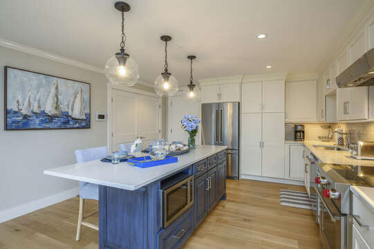 Large luxury style kitchen with center island with microwave, chefs range with oven and stainless fridge. Separate laundry behind the double doors. Unit 204, 557 Route 28 Harwich Port, Cape Cod ,New England Vacation Rentals
