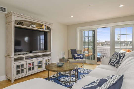Bonus room with large flat screen tv, sectional with chaise lounge, leather chair  and entrance to private roof top terrace.Unit 204,557 Route 28, Harwich Port, Cape Cod, New England Vacation Rentals