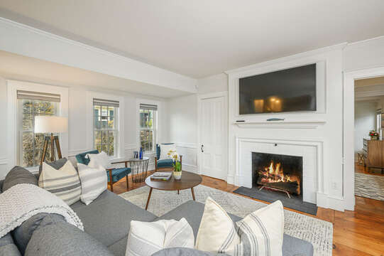 Living room with comfy chaise lounge style couch and 2 end chairs, large flat screen tv and original fireplace. Entrance to Bedroom #1. 530 Route 28 Harwich Port, Cape Cod, New England Vacation Rentals