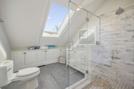 En suite bath for bedroom #3 with large tiled walk in shower, vanity, skyligt and build in cabinets. 530 Route 28 Harwich Port, Cape Cod, New England Vacation Rentals