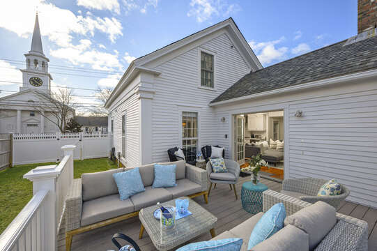 The Pineapple house side deck with ample comfortable seating for relaxing after a long day on Cape Cod 530 Route 28 Harwich Port, New England Vacation Rentals.
