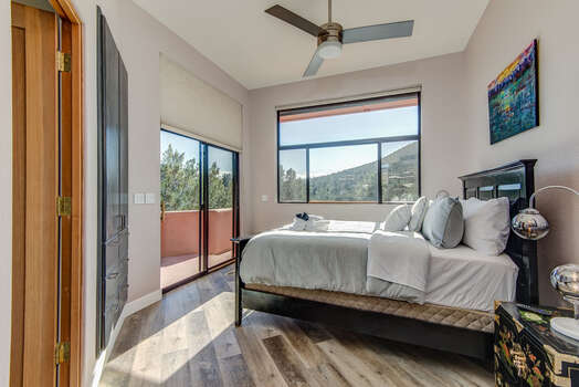 Main Level Bedroom 2 with a Queen Bed, Full Shared Bath Nearby, and Patio Access with Mountain Views