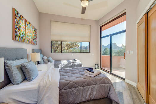 Main Level Bedroom 3 with Two Twin Beds (or a King Upon Request and a Fee), Full Shared Bath Nearby, and Patio Access with Mountain Views