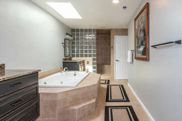 Master Suite Bath with his and her sinks, large tub, walk-in shower, and enclosed toilet.
