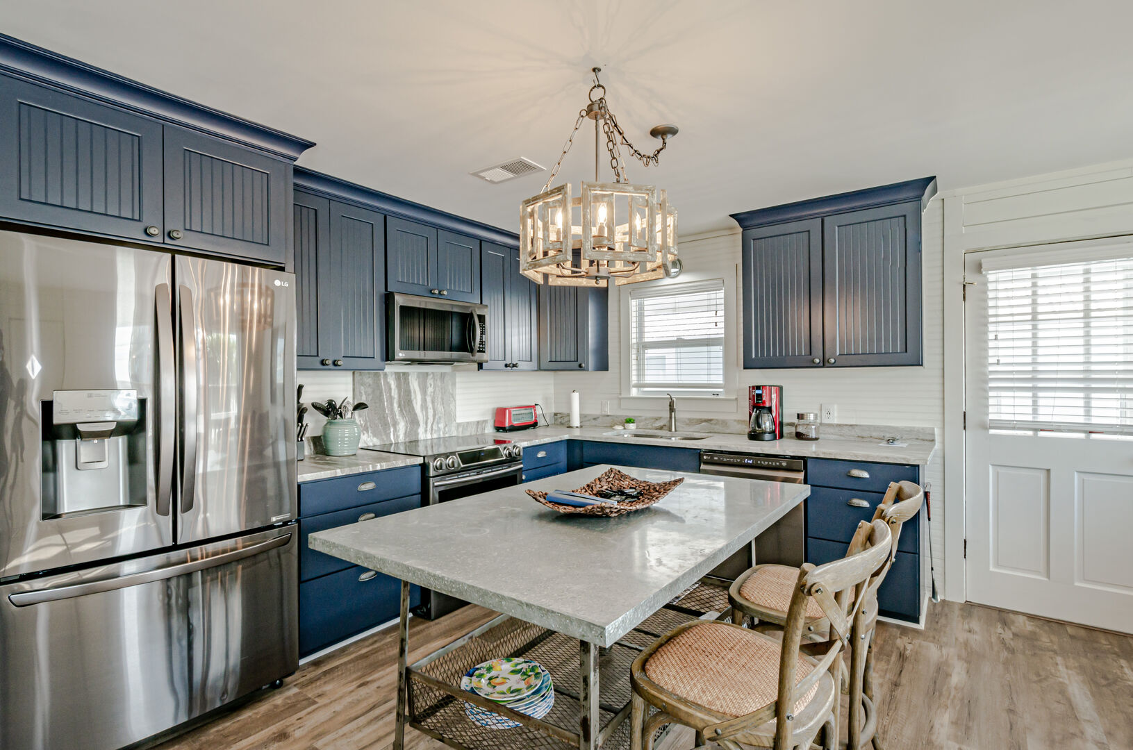 Gorgeous gourmet kitchen with modern appliances, blue cabinets, and center table island.