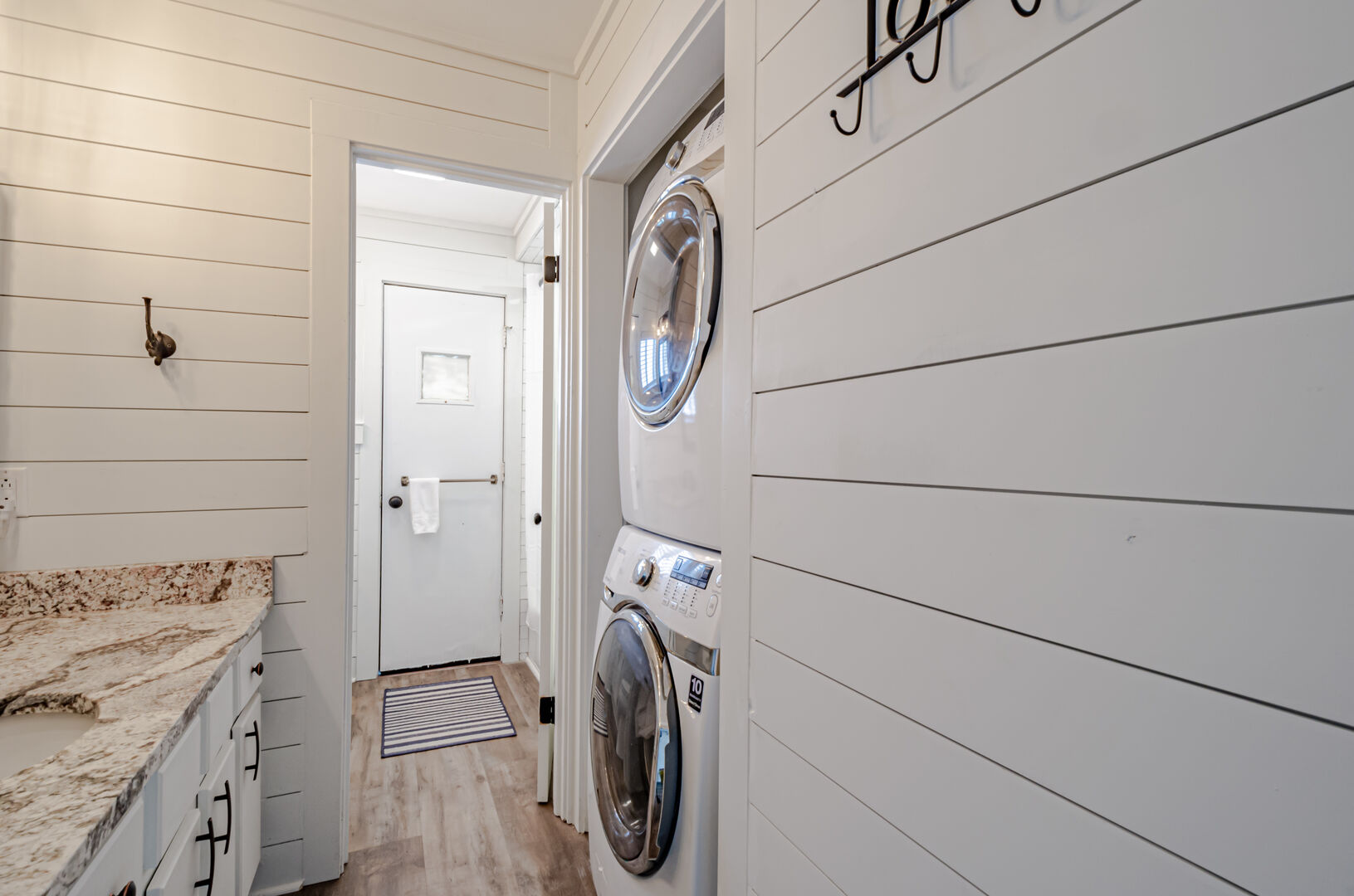 Laundry machine located in hall bathroom.