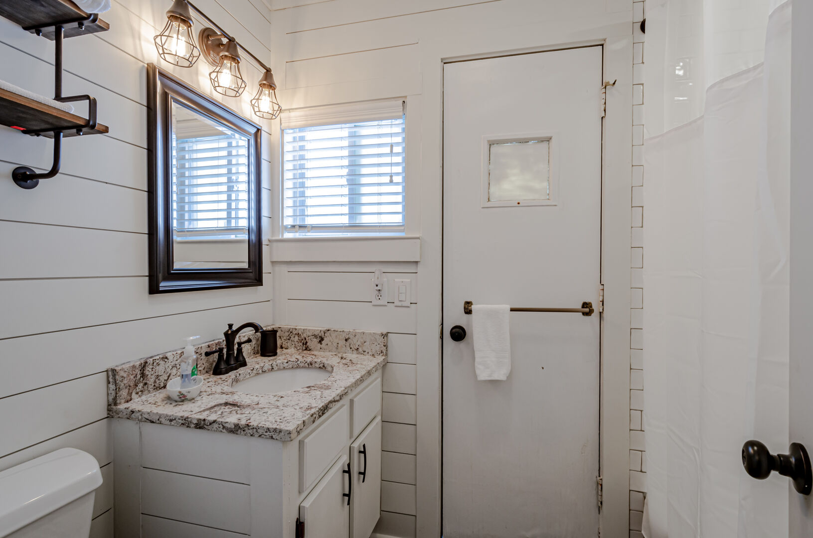 Shared hall bathroom with sink and toilet.