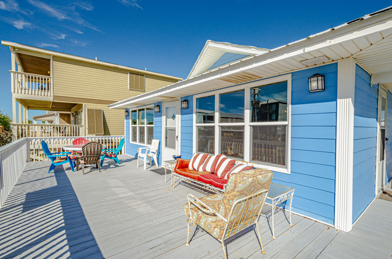 Porch and seating of this Gulf Shores Beach House Rental, with the homes bright blue paint job visible.