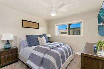 Queen bed in Guest Room with a flat screen Smart TV.