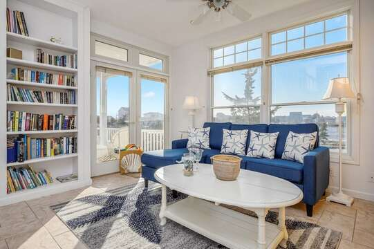Living room with comfy chaise couch with full pull out bed, ample books for reading and entrance to back deck overlooking the tranquil marsh.27 Fiddlers Green Lane-Dennis Port-New England Vacation Rentals