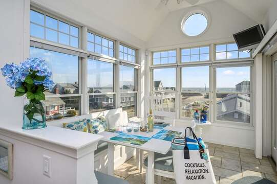 Bright and open concept dining area with panoramic views of the ocean, seating for 6 at the corner dining table with bench seat.27 Fiddlers Green Lane-Dennis Port-New England Vacation Rentals