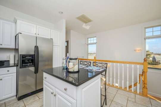 Open concept Kitchen with center island and stairs to lovwer level.27 Fiddlers Green Lane-Dennis Port-New England Vacation Rentals