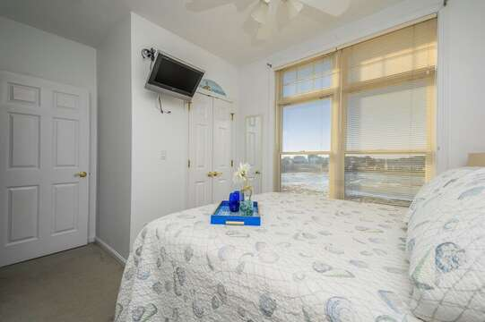 Queen bed with flat screen TV and closet with marsh views  27 Fiddlers Green Lane-Dennis Port-New England Vacation Rentals