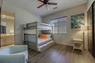 Bedroom 5, located next to bedroom 4, features a Full Over Full with Twin Trundle Bunk Bed and a 50-inch TCL by Roku Smart television. Bedroom 5 and 4 are joined by a jack and jill bathroom.