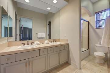 The jack and jill bathroom  features a combo shower and tub and double vanity sinks