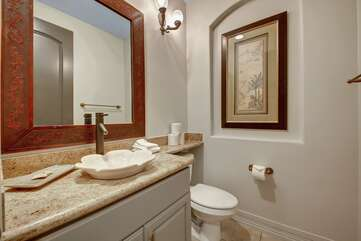 The Hallway powder room, located just off the living room, features a designer vanity sink.