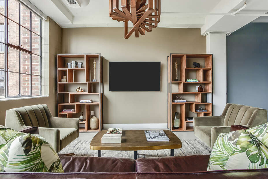 Living Area with Leather Sofa, two Chairs, TV, and Bookshelves