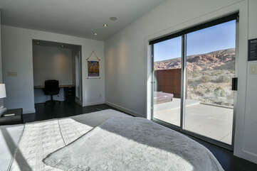 Master bedroom with an entrance to the patio and desk