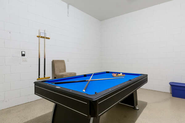 The garage has been converted into a game room with a pool table and comfortable seating