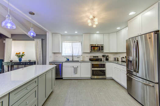 Fully Equipped Kitchen with Stainless Steel Appliances, including an Electric Range with Double Ovens and a Refrigerator with an Ice Maker