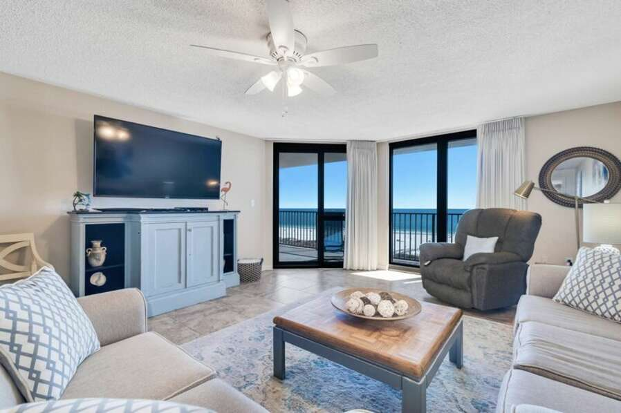 Spacious Living Room offers Comfortable Seating, Beachfront Views and Balcony Access