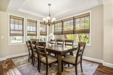 The dining area, with seating for 8 and large windows looking out onto tropical landscaping.