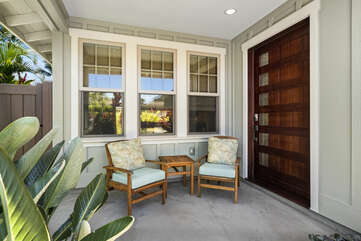 Chairs sit on the front porch by a large ornate door.