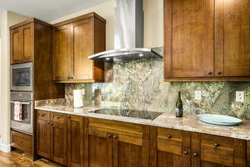 The oven range, built into the countertop, next to the microwave, and an oven built into the cabinetry.
