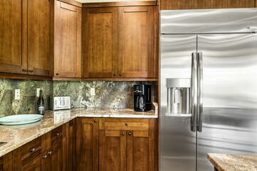 The large stainless steel fridge of the kitchen, next to the coffee maker.