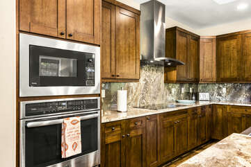 Angled photo of the kitchen, displaying the oven, microwave, and range built into the counter.