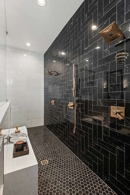 The ensuite bathroom has dual shower heads in the walk-in shower